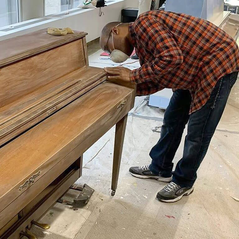 Cory sands down his piano to prepare it for painting