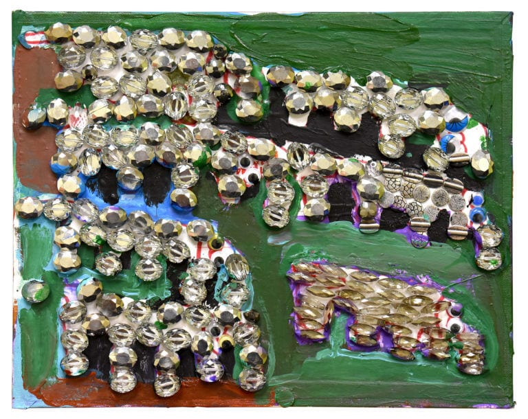 7 elephants made from gems and googly eyes stand in a field of green and brown