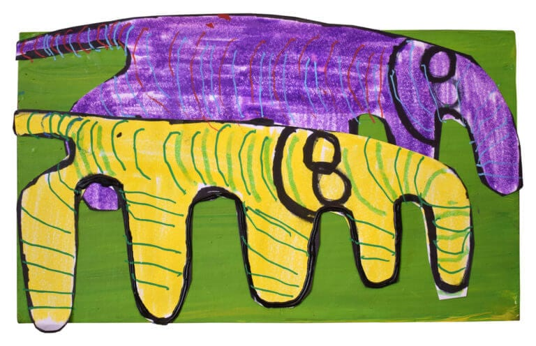 A purple elephant and a yellow elephant, made of paper cut-out, stand on a green piece of wood