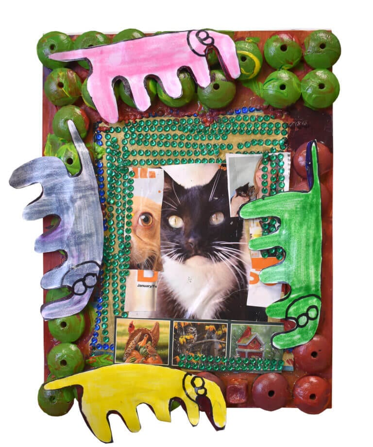 A collage of animals, featuring a cat, framed by cut-paper elephants and painted beads