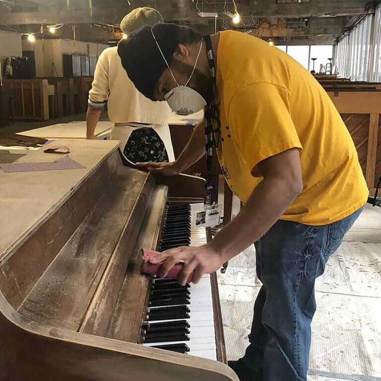 Jayson Valles sands a piano, preparing his three-dimensional canvas for painting