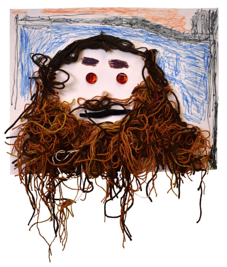 Depiction of a face with yarn for beard, buttons for eyes and a corn for nose